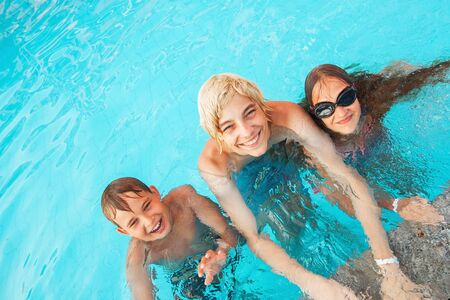 Children Having Fun In Outdoor Swimming Pool. Boy and girl in summer vacation