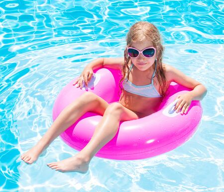 Girl on inflatable ring in swimming pool. Vacations