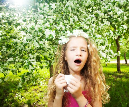 Sneezing girl near blowing tree. Child with a handkerchief. Allergy