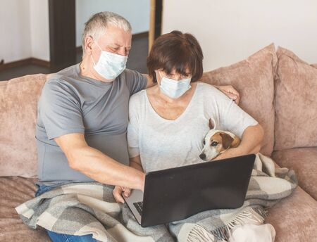 Coronavirus CoVid-19 Couple old aged senior people at home with seasonal winter cold illness looking at laptop disease sit down on the sofa. Elderly couple in medical masks during the pandemic