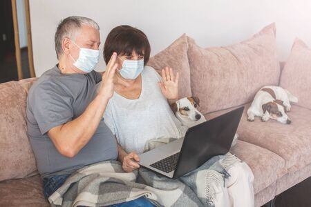 Couple old aged senior people at home with seasonal winter cold illness talking sit down on the sofa. Elderly couple in medical masks during the pandemic Coronavirus CoVid-19 스톡 콘텐츠