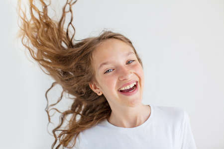 Portrait of beautiful cheerful girl with flying curly hair smiling laughing looking at camera over white background
