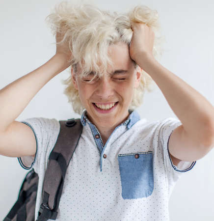 Frustrated student covered his face with his hands. Sad teen at white background Zdjęcie Seryjne
