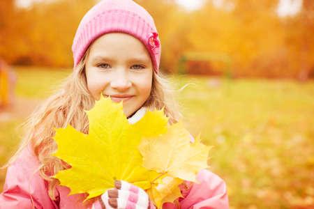 Girl at autumn. Little child outdoors