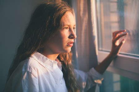 Sad teen near window. Unhappy girl at home Zdjęcie Seryjne