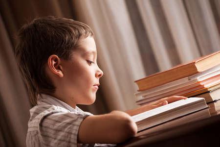 Boy reading book. Child learning homework