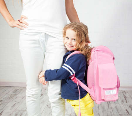 Mother helps her daughter get ready for school. Schoolgirl afraid to go to school
