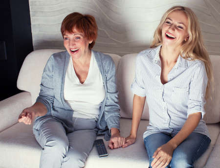 Mother with adult daughter watching television. Women looking film comedy Zdjęcie Seryjne