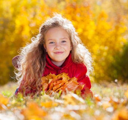 Girl at autumn. Child with leaf at park Zdjęcie Seryjne