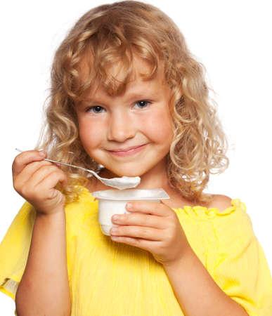 Little child eating yogurt isolated on white Zdjęcie Seryjne