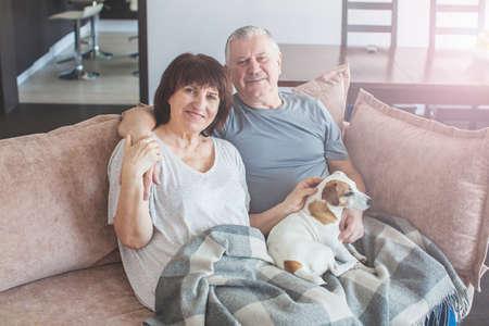 Happy elderly couple sitting on sofa at home. Seniors with dog