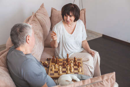 Elderly couple playing chess at home. Happy couple seniors