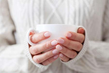 Coffee mug in female hands. Woman drinking hot coffee