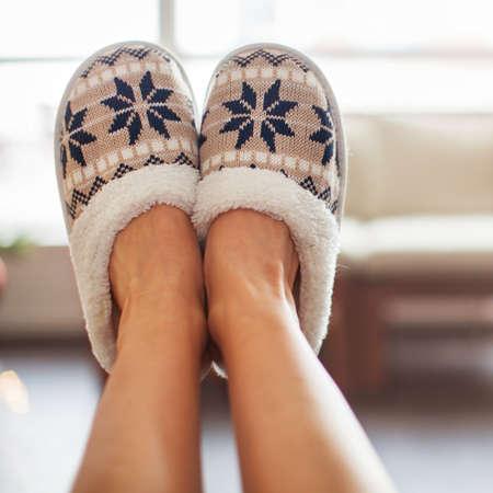 Slippers on womens legs. Soft comfortable home slipper Zdjęcie Seryjne
