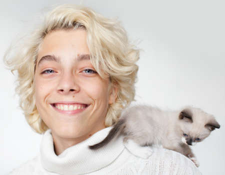 Cute cat at the shoulder young man. little kitten with teen