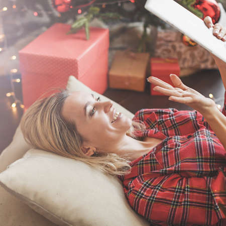 Woman in front of christmas tree on living room, using tablet pc.