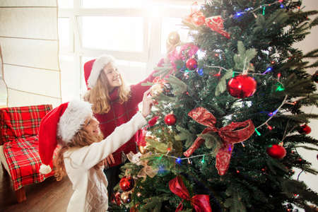 Children decoration christmas tree. Little girl at home. Happy New Year!