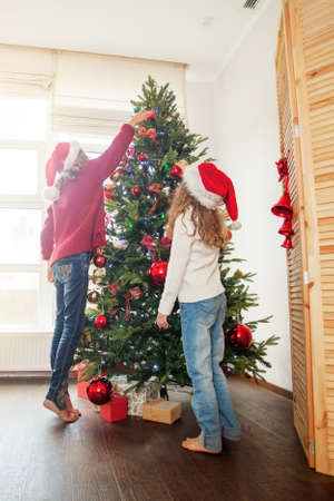Family decoration christmas tree. Little girl at home. Happy New Year!