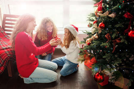 Family decoration christmas tree. Child with mother in christmas hat at home