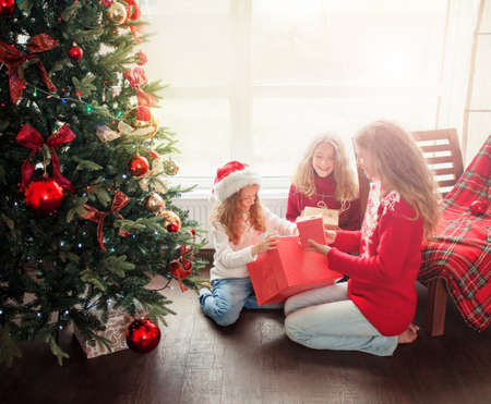 Child with mother at home near christmas tree. Family with christmas gift