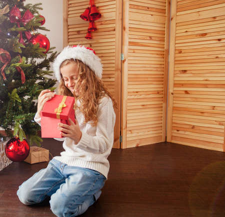 Child with gift near christmas tree. Girl at home. New year!