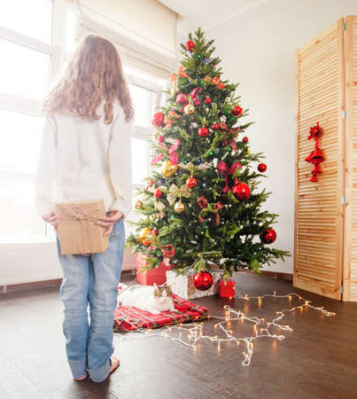 Child near the Christmas tree with a gift behind. Girl back