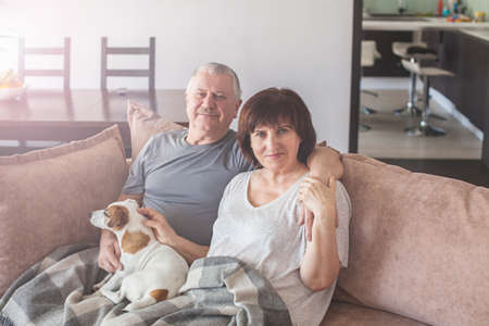 Happy elderly couple sitting on sofa at home. Seniors with dog