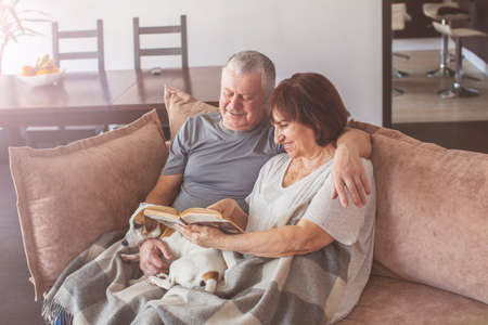 Happy elderly couple sitting on sofa and reading book at home. Seniors with dog
