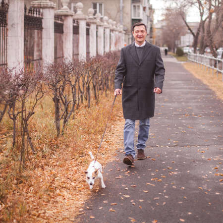 Man walks with his dog. Guy on the street with pet 免版税图像