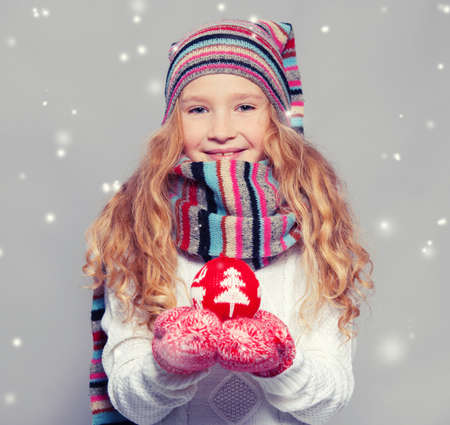 Girl in winter clothes with christmas ball