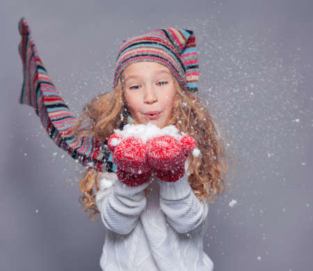 Girl blowing on the snows. Happy child in winter clothes. Studio shot