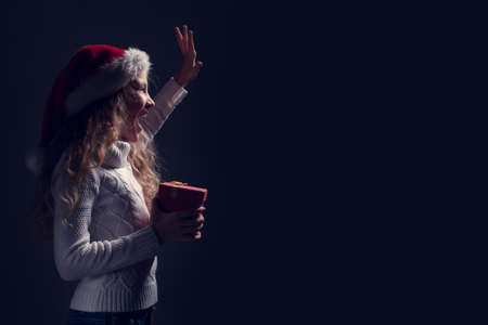 Happy child in christmas hat with gift at night. Girl waving goodbye 免版税图像