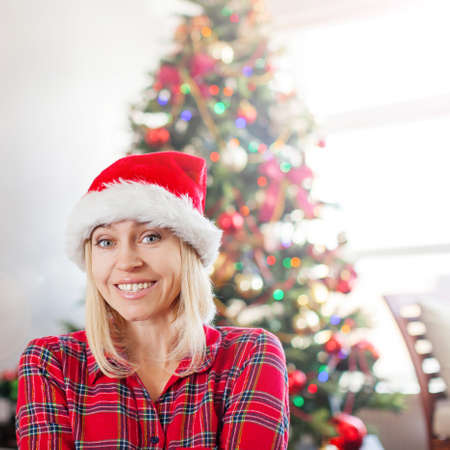 Happy woman on Christmas tree background. Female at home
