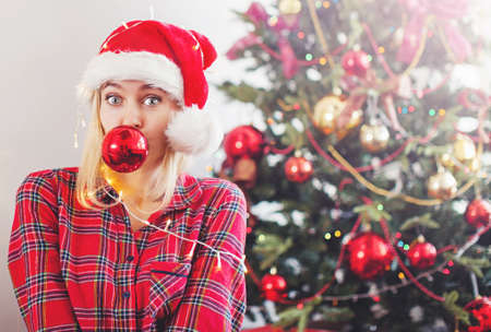 Happy woman wrapped in Christmas lights. Female at home in christmas decoration