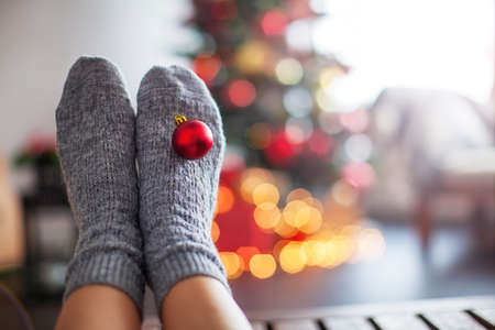 Knitted socks on Christmas tree background. Comfort home textiles