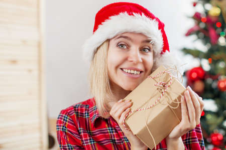 Happy woman on Christmas tree background. Female at home with gift