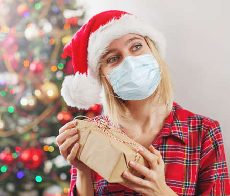 Gift on female hands. Happy Christmas. Woman at mask coronavirus covid 19