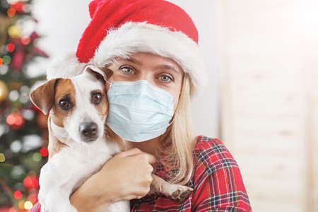 Female with dog. Happy Christmas. Woman at mask coronavirus covid 19 免版税图像