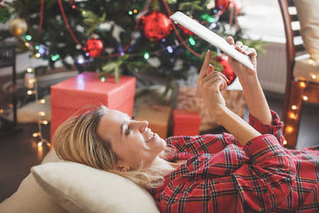 Woman in front of christmas tree on living room, using tablet pc