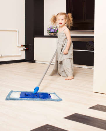 Girl washes a floor mop. Helps the child to do housework