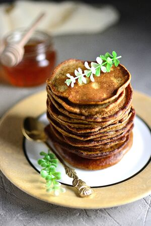 Chocolate pancakes stacked on a plate with honey