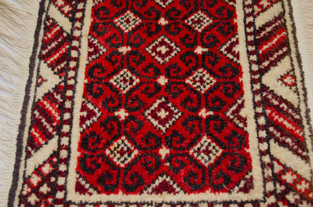 Small wool rug handmade with red background photo