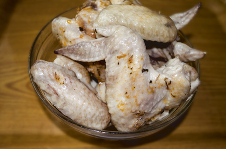 glass plate: Boiled chicken wings in glass plate at plastic surface