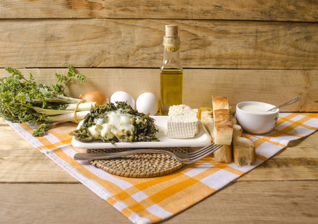 sour milk: White dishes with shoots of edible spring grass and sour milk on the rough wooden boards