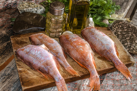 Processed carcasses of red grouper with herbs and spices on the kitchen board Stock Photo