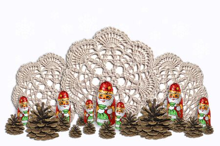 Chocolate Santa Clauses with fir cones on the background of knitted napkins