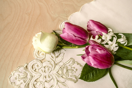 plywood: Purple tulips with white rose and hyacinth on the corner embroidered tablecloth lay on plywood Stock Photo