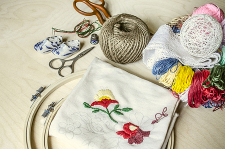 Colored thread, needles, scissors and frame necessary tools for decorative embroidery