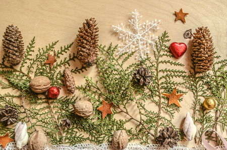 Christmas background of wooden plywood with chocolate hearts and balls,pine cones, nuts with snowflake lying on the branches of a thuja