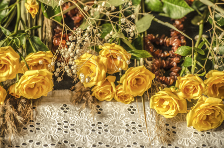 White embroidered border covered with amber beads with yellow roses, dry branches of white hypsophila and reeds on a black background